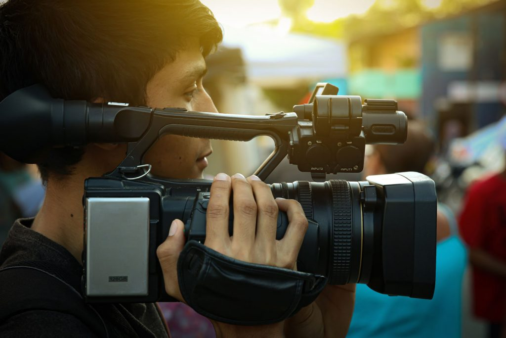 Young guy holding a video camera.
